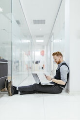 Businessman in office sitting on floor, using laptop - ZEDF00653