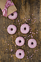 Doughnuts with pink icing and sugar granules and baking decor on wood - LVF06171