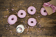 Doughnuts with pink icing and sugar granules and a bottle of milk on wood - LVF06174