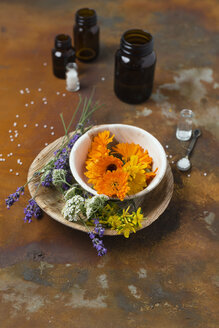 Blossoms of medical plants, medicine flasks and globules on rusty ground - MYF01933