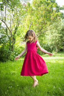 Little girl wearing red summer dress dancing on a meadow - LVF06182