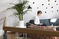 Woman using laptop on couch in modern office - FKF02344