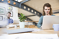 Colleagues working in modern office - FKF02356