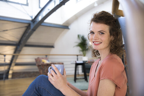 Portrait of smiling woman having a coffee break in modern office - FKF02359