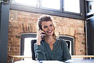 Young woman on the phone at desk in office - FKF02380
