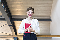 Portrait of smiling businesswoman holding notebook - FKF02389