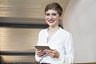 Portrait of smiling businesswoman holding tablet - FKF02392