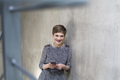 Portrait of smiling woman holding cell phone at concrete wall - FKF02395