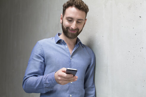Smiling man looking at cell phone at concrete wall - FKF02398