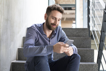 Smiling man sitting on stairs looking at cell phone - FKF02401