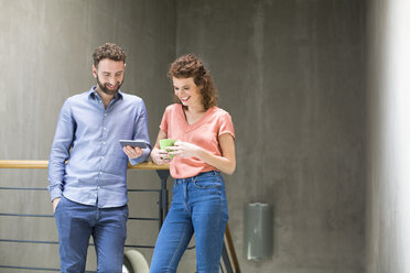 Man and woman in staircase with cell phone and cup of coffee - FKF02407