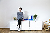 Smiling woman sitting on cabinet in office - FKF02413