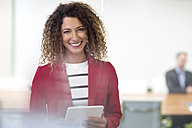Portrait of smiling businesswoman with tablet in office - ZEF13997
