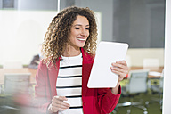 Smiling businesswoman with tablet in office - ZEF14000