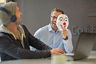Businessman surprising colleague with mask - ZEF14012