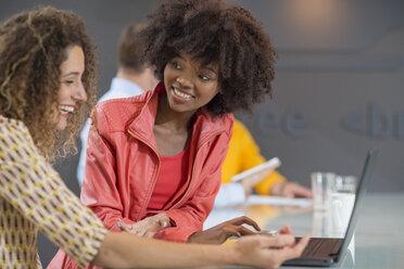 Two happy women in office sharing laptop - ZEF14015