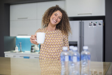 Portrait of smiling woman in office kitchen holding cup - ZEF14018