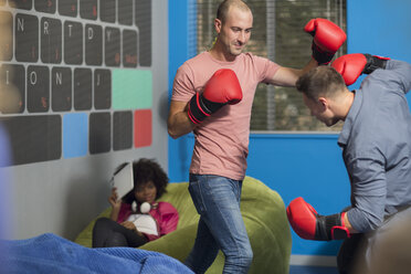 Colleagues boxing in office lounge - ZEF14033