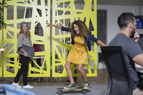 Woman on skateboard in office having fun - ZEF14036