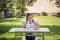 Girl with stack of donuts on garden table - LVF06192