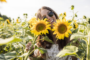 Happy woman in a sunflower field - MAUF01075
