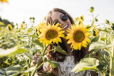 Happy woman in a sunflower field - MAUF01075