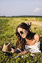 Happy woman lying in a field looking at instant photos - MAUF01078