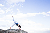 Woman doing a yoga exercise on a rock - ABZF02132