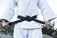 Man tying his black belt during a martial arts training - ABZF02135
