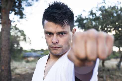 Challenging man showing his fist doing a martial arts pose - ABZF02138