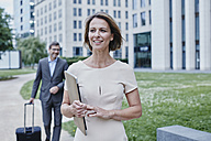 Smiling businesswoman outdoors with laptop and businessman in background - RORF00876