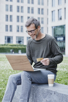 Mature man outdoors with laptop, credit card and takeaway coffee - RORF00882