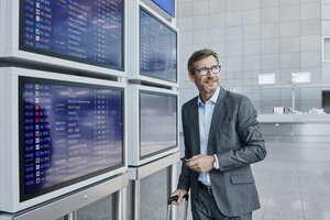 Businessman with cell phone at timetable at the airport - RORF00885