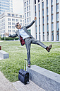 Playful mature businessman with rolling suitcase balancing on wall taking a selfie - RORF00894