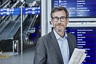 Smiling businessman with newspaper at timetable at the airport - RORF00897