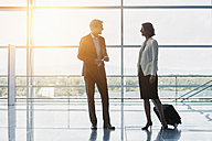 Businessman and businesswoman talking at the airport in backlight - RORF00903