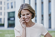 Smiling businesswoman on cell phone outdoors - RORF00909