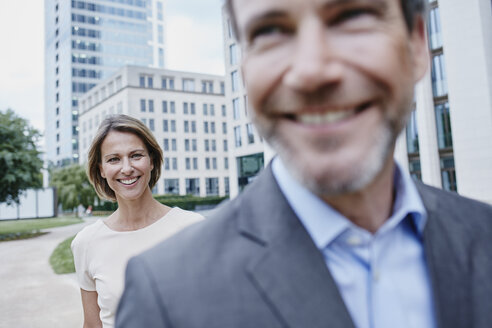 Happy businesswoman and businessman outdoors - RORF00918