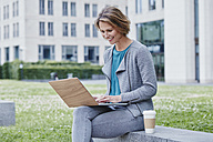Happy woman outdoors with laptop and takeaway coffee - RORF00933