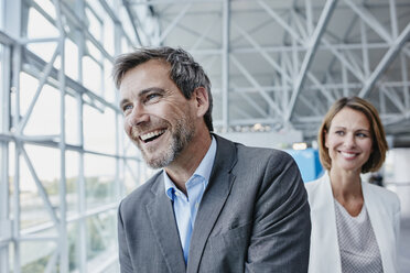 Happy businessman and businesswoman at the airport - RORF00945