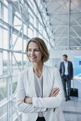 Smiling businesswoman at the airport looking out of window - RORF00948