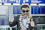 Happy businessman dressed up as tourist at the airport - RORF00951