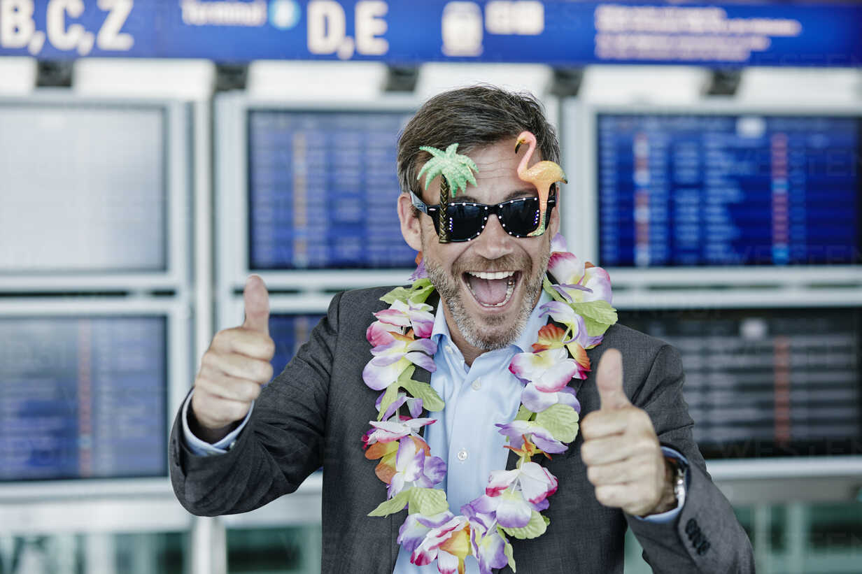 Happy businessman dressed up as tourist at the airport - RORF00951 - Roger Richter/Westend61