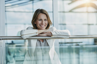 Happy businesswoman leaning on railing at the airport - RORF00957