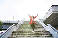 Excited woman in the city jumping on stairs - HAPF01709