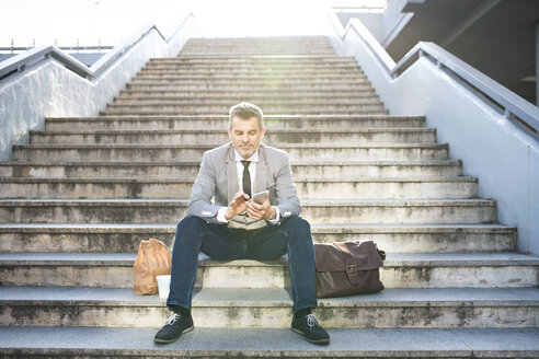 Confident businessman in the city sitting on stairs using cell phone - HAPF01712