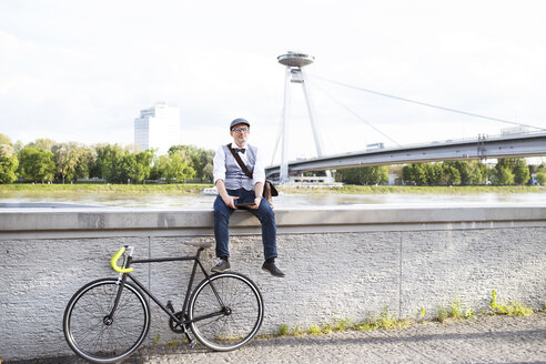 Businessman with bicycle and tablet at the riverside - HAPF01724