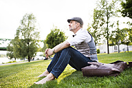 Mature businessman in the city park sitting on grass - HAPF01727