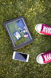 Smartphone, tablet with photography and feet in grass - HAPF01733