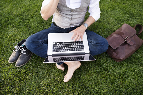 Unrecognizable businessman with laptop sitting on grass - HAPF01736